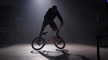 BMX rider doing tricks in dark warehouse. video