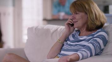 donna anziana in soggiorno che parla al cellulare video