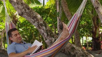 man sitter i hängmatta läser bok, costa rica video