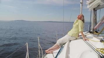 senior kvinna som kopplar av på segelbåt. video