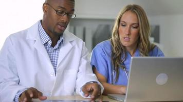 Doctor and nurse looking at x-ray in office video