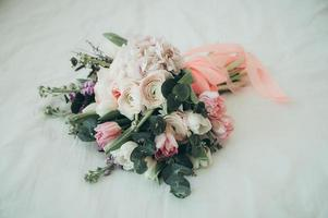A bridal bouquet on a bed photo