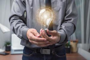 Businessman holding a light bulb and thinking of new ideas photo