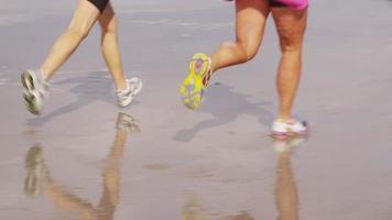 dos mujeres corriendo juntas en la playa. video
