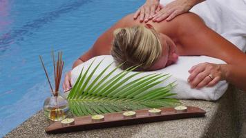 donna che posa in piscina per ottenere un massaggio alla schiena. video