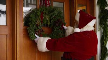 jultomten sätter krans på dörren video