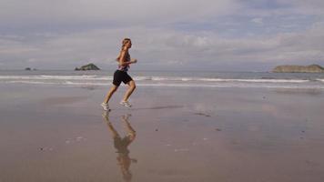 mujer corriendo en la playa, cámara lenta video