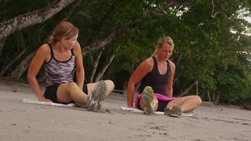 mujer estirando y preparándose para correr en la playa. video