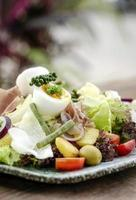 Nicoise style healthy organic rustic salad with egg and ham outdoors photo
