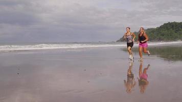 tiro de cámara lenta de amigos corriendo juntos en la playa. video