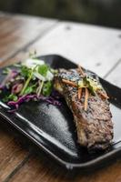 Marinated grilled barbecue pork rib with salad and pickled vegetables photo