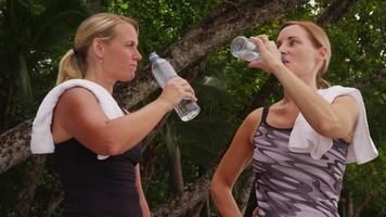 mujer descansando y bebiendo agua después de correr. video