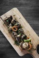 Salchicha fresca a la parrilla, aperitivo de tapas de arranque en tablero de madera rústica foto