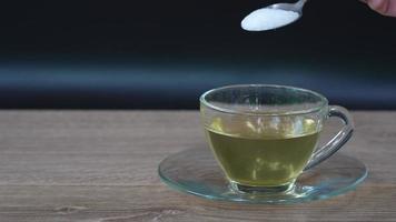slow motion van mensen voegen suiker toe in hete thee op tafel video
