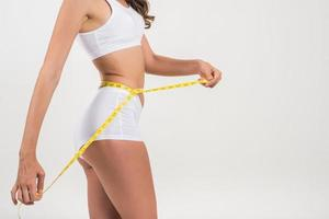 Beautiful young woman measuring her figure size with tape measure. photo