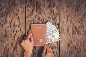Top view passport with money on wood background, tourism concept. photo