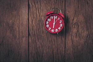 vista superior reloj despertador rojo sobre fondo de madera. foto