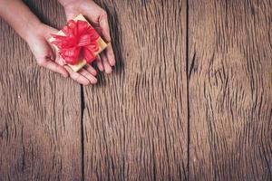 vista superior mano sujetando la caja de regalo sobre fondo de madera. foto