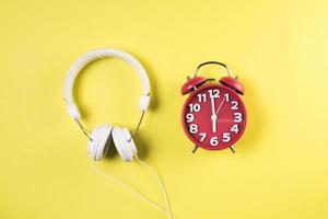 vista superior reloj despertador rojo con auriculares. foto