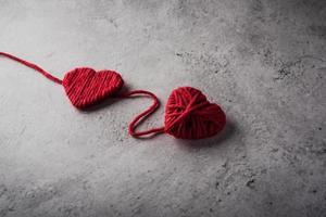 Hilo rojo en forma de corazón en el fondo de la pared. foto