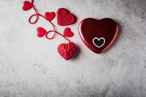Red yarn heart shaped on the wall background. photo