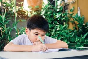 lindo asiático adolescente haciendo su tarea foto
