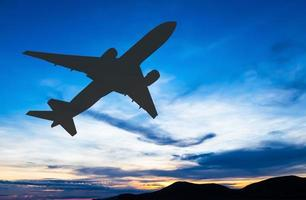 Silhouetted commercial airplane flying at sunset photo