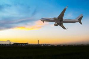 Commercial airplane flying over the airport at sunset photo