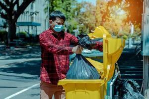 The man took the black bag to throw away the garbage photo