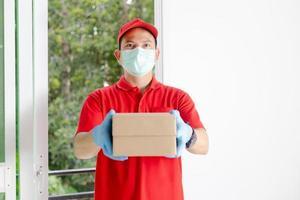 un repartidor vestido con una camisa roja y un sombrero sostiene una caja de paquetería foto
