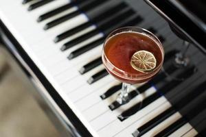 una copa de cóctel alcohólico en el fondo de un piano. foto