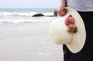 Young woman holding hat on the beach photo