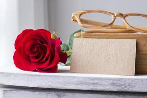 Red rose and blank brown paper on vintage cabinet photo