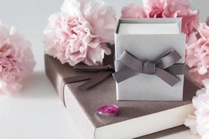 Caja de regalo y flores de clavel sobre fondo blanco. foto