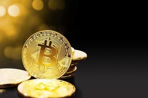 Gold bitcoin on black background with copy space photo