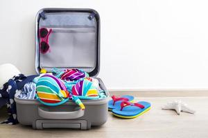 Bikini de colores y ropa en el equipaje en el piso laminado. foto