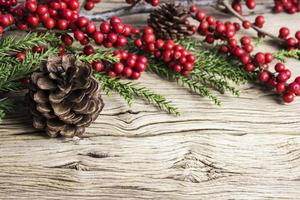 Christmas decoration of pine cone and red winterberry on old wood photo