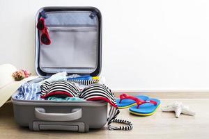 bikini y ropa en el equipaje en el piso laminado foto