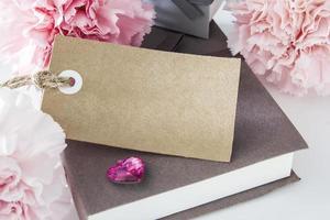etiqueta de papel en blanco con caja de regalo y flores de clavel foto