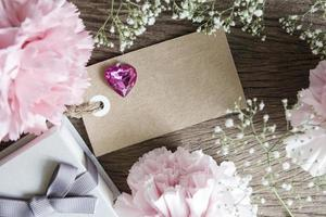 Blank paper tag with gift box and carnation flowers photo