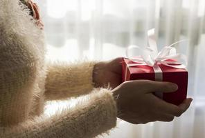 Young woman hands holding red gift box photo