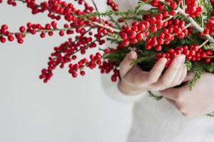 Woman hands holding ilex verticillata or winterberry photo