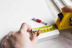 Young woman measuring home furniture with measure tape photo