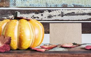 Thanksgiving and autumn concept of blank brown paper tag and pumpkin photo