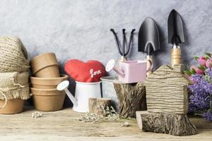 Home and garden concept of wood home and gardening tools and flowers photo