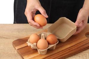Mujer sosteniendo huevos de gallina en caja de cartón sobre fondo blanco. foto