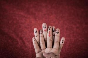 dedo con emoción sobre fondo rojo. foto