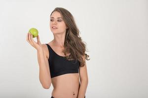 mujer de belleza sosteniendo manzana verde mientras aislados en blanco. foto