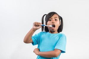 little girl brushing her teeth in studio shot. photo