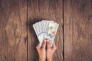 Hand holding dollar banknote money on wood background photo